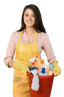 Amichevole giovane donna delle pulizie che tiene gli accessori per la pulizia - isolato