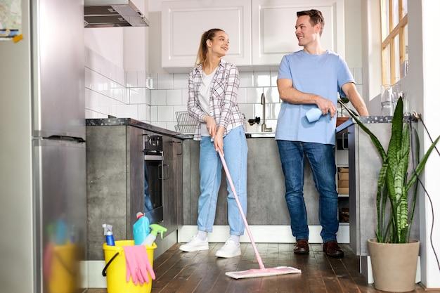 Amichevole giovane coppia che pulisce casa in cucina donna che pulisce il pavimento con il marito mop che aiuta