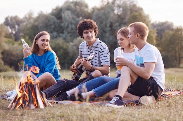 I giovani amichevoli hanno espressioni gioiose, trascorrono del tempo libero durante il fine settimana insieme, siedono vicino al fuoco
