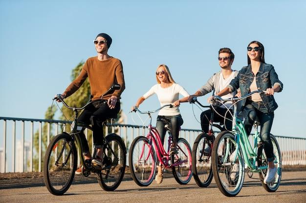 Amici in bicicletta. integrale di quattro giovani che vanno in bicicletta e sorridono