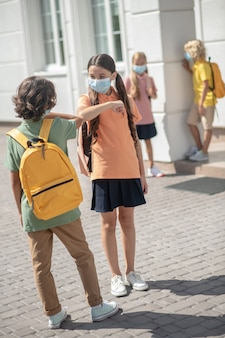 Amici. un ragazzo e una ragazza in maschera si salutano nel cortile di una scuola