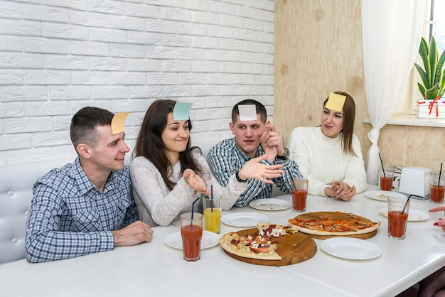 Amici al bar che mangiano pizza e giocano a indovinare chi