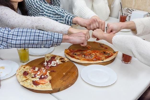 Amici al bar che mangiano pizza e posano per la macchina fotografica