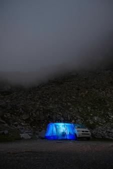 Amici in campeggio di notte in montagna, dentro una tenda e un camper. (neouvielle, pirenei francesi)