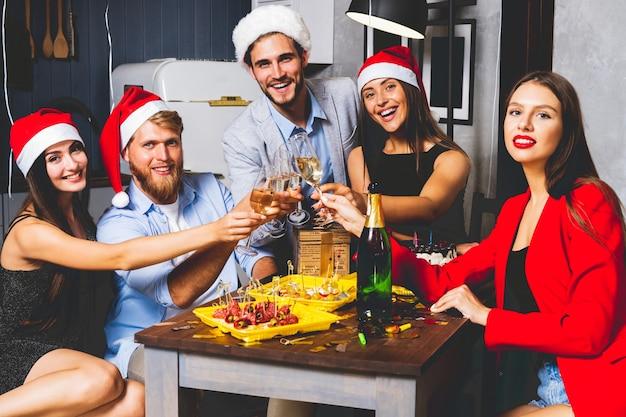 Amici che celebrano il natale o il capodanno. tavolo da festa con champagne