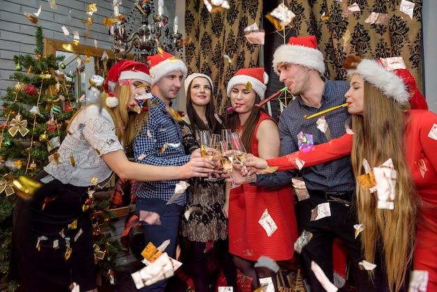 Amici che celebrano il nuovo anno con scintillii che cadono