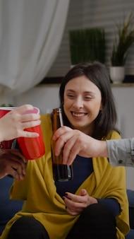 Amici che chiacchierano durante la festa notturna seduti sul divano in soggiorno bevendo birra divertendosi