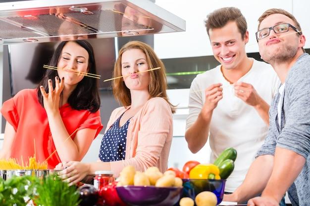 Amici che cucinano spaghetti e carne nella cucina domestica