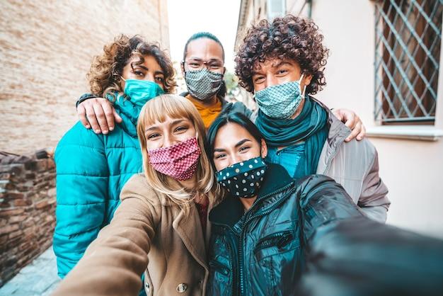 Amici coperti da maschere che si scattano un selfie fuori in città