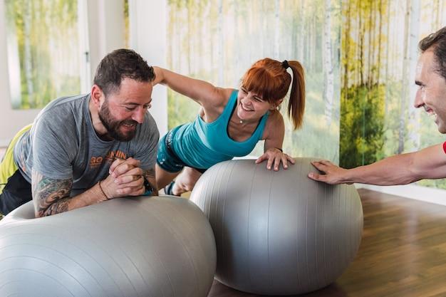 Amici che fanno esercizi di pilates di equilibrio insieme in palestra con un allenatore che li motiva