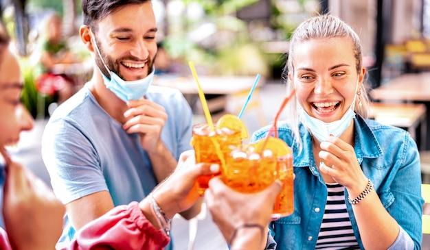Amici che bevono al cocktail bar con maschere facciali aperte