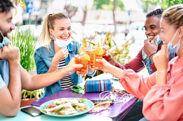 Amici che bevono spritz al cocktail bar con maschere