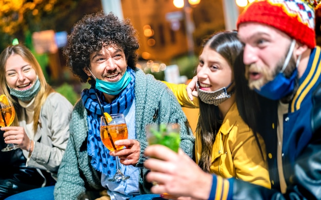 Amici che bevono spritz e mojito al cocktail bar con maschera facciale aperta - focus sul ragazzo di sinistra