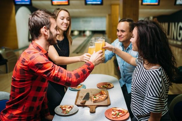 Gli amici beve e mangia la pizza nel club di bowling