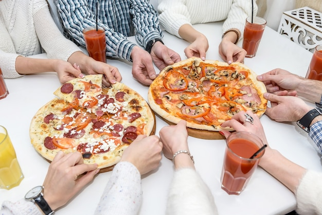 Gli amici mangiano pizza e bevono succo di frutta nella caffetteria