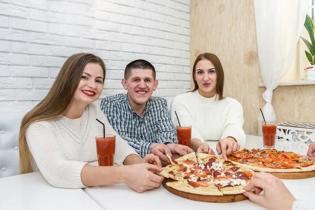 Gli amici mangiano pizza e bevono succo al bar