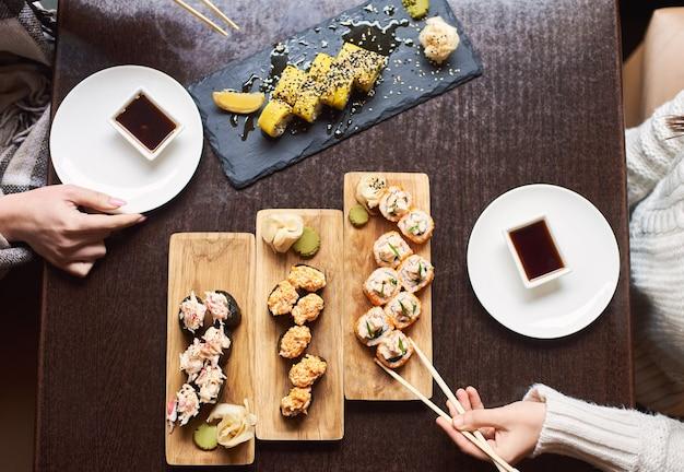 Amici che mangiano piatto giapponese da riso e frutti di mare.