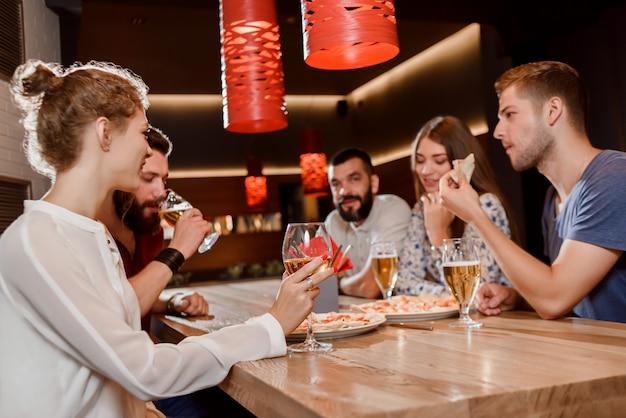 Amici che mangiano pizza e che bevono birra in pizzeria.