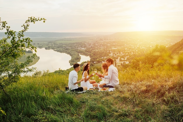 Amici che si godono la giornata del picnic e bevono vino bianco insieme.