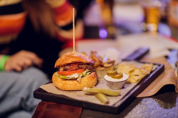 Amici che godono insieme nel delizioso gusto di hamburger.