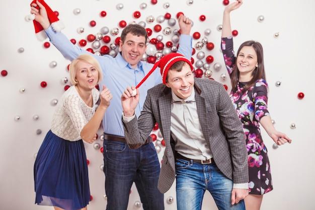 Gli amici di quattro uomini e donne ballano e ridono divertendosi in stile natalizio