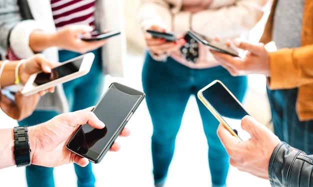 Gruppo di amici che condividono contenuti su smart phone mobile