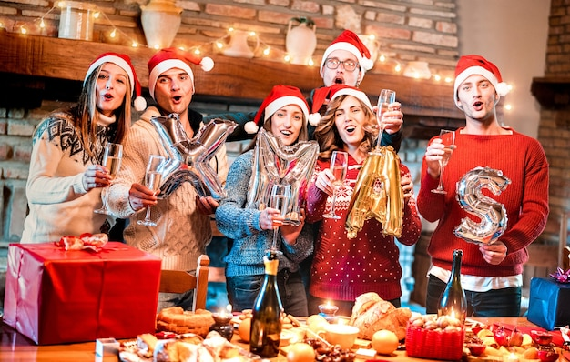Gruppo di amici con cappello santa che celebra il tempo di natale con champagne e dolci a cena