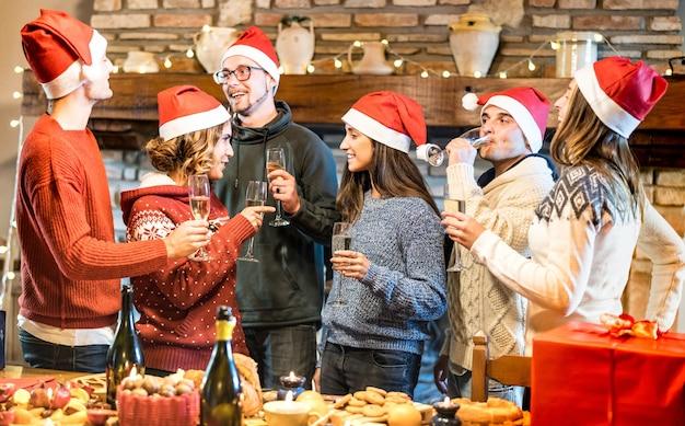 Gruppo di amici con cappelli di babbo natale che celebrano il natale con brindisi di vino champagne a cena a casa