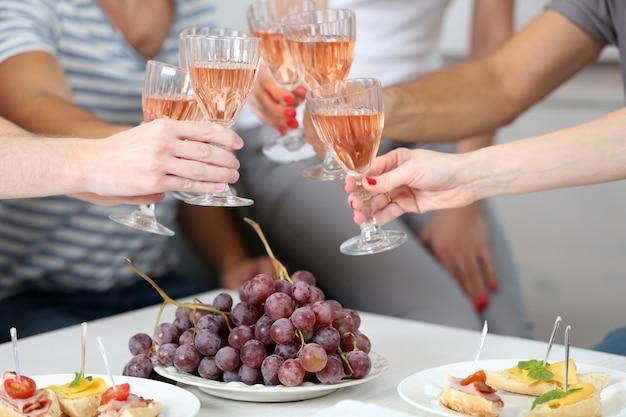 Mani degli amici con bicchieri di vino e snack, primi piani