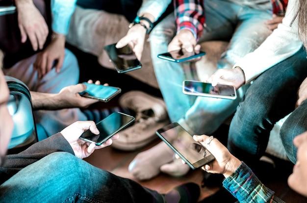Amici che hanno divertimento dipendente utilizzando smartphone mobile a casa