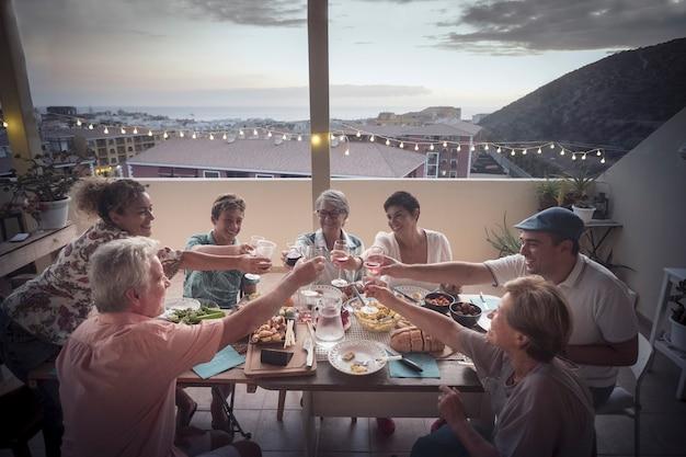 Amici che fanno una festa barbecue al tramonto nel patio dell'attico