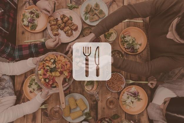 Amici a cena. vista dall'alto di quattro persone che cenano insieme seduti al tavolo di legno rustico