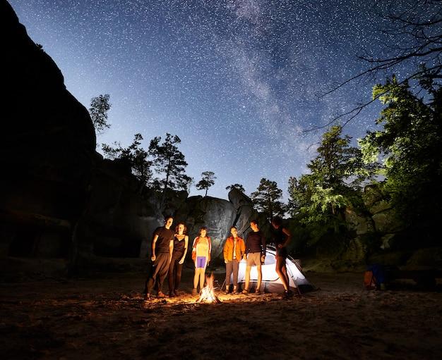 Escursionisti di amici a riposo accanto al campo, falò, tenda di notte