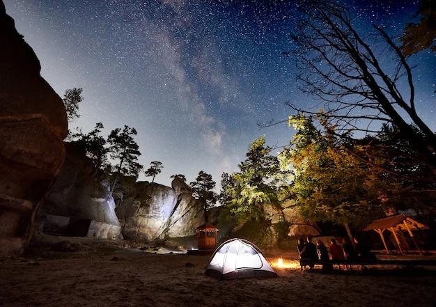 Escursionisti di amici a riposo accanto al campo, fuoco, tenda di notte