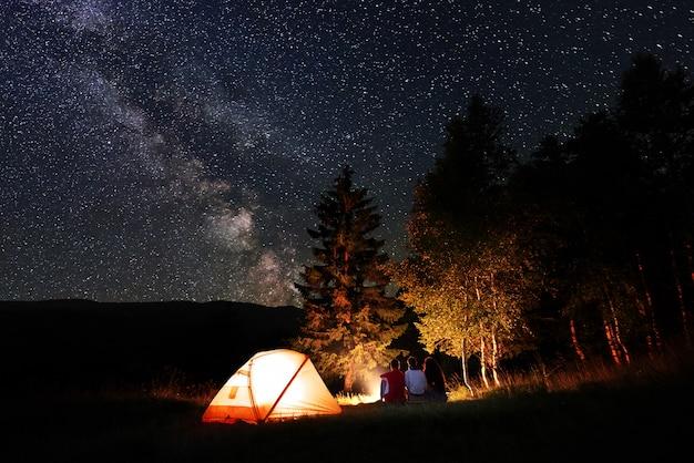 Amici escursionisti seduti accanto al fuoco di notte vicino alla foresta e tenda illuminata