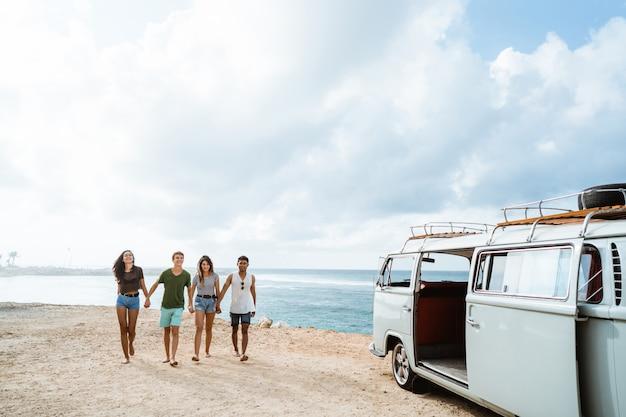 Amici che si tengono per mano e che camminano in spiaggia un giorno soleggiato