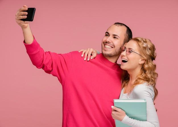 Amici che ridono mentre prendono selfie