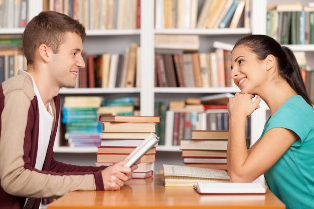 Amici in biblioteca. allegro giovane uomo e donna seduti alla scrivania della biblioteca e sorridenti a vicenda