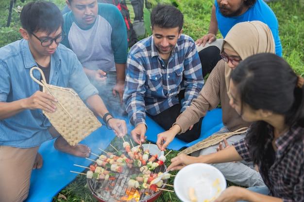 Amici che fanno un barbecue insieme all'aperto