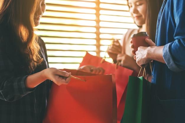 Amici che aprono e guardano insieme le borse della spesa