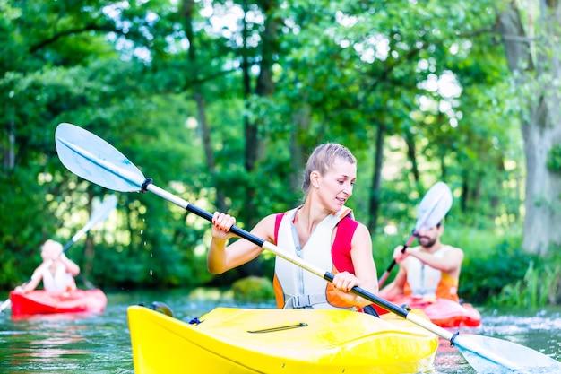 Amici che remano con la canoa sul fiume della foresta