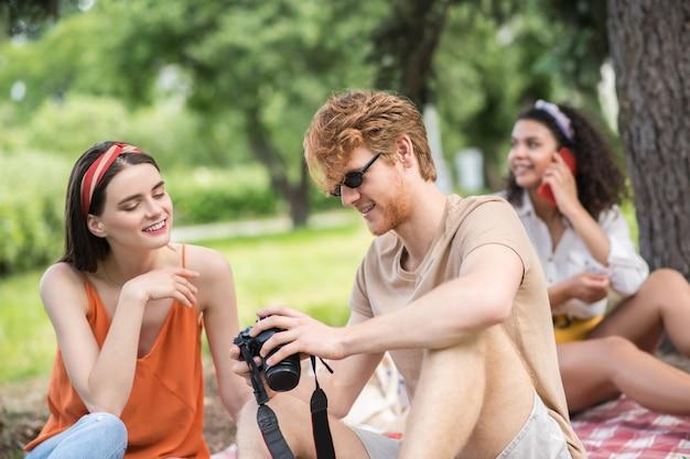 Amici, picnic. ragazzo sorridente dai capelli rossi che mostra la macchina fotografica alla ragazza e alla ragazza dai capelli lunghi interessati che parlano sullo smartphone dietro al picnic