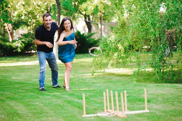 Amici che giocano giochi all'aperto - lancio dell'anello nel parco estivo.