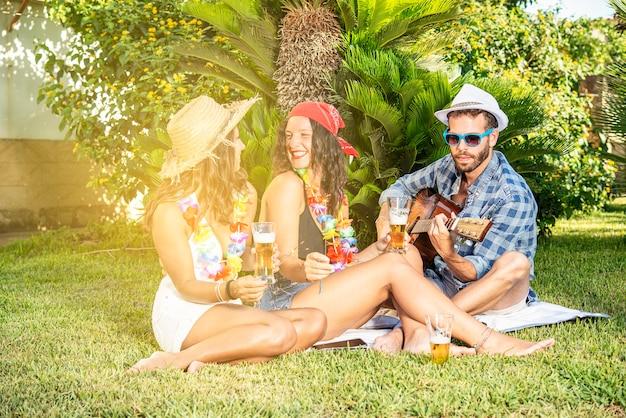 Gli amici suonano la chitarra sull'erba durante un picnic. tempo libero e spensieratezza in totale libertà
