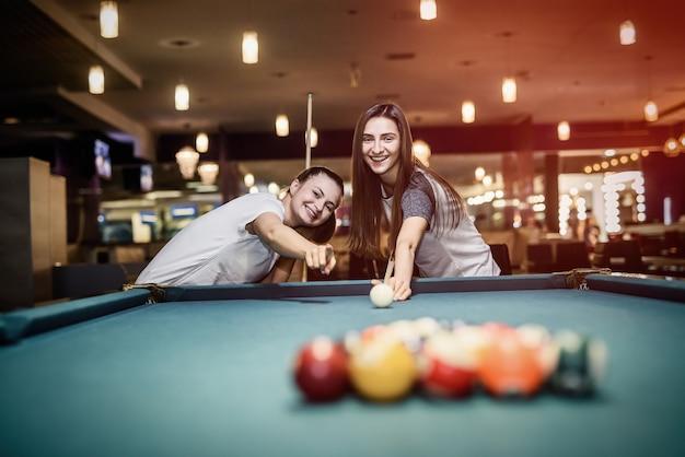 Amici che giocano a biliardo che mira sulla palla nel pub