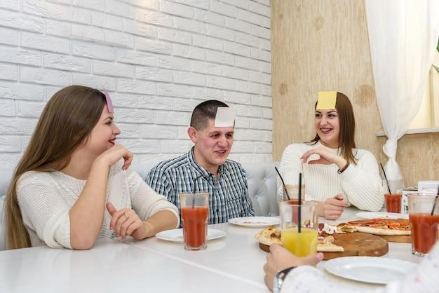 Amici che giocano a indovinare chi sono e si divertono al bar