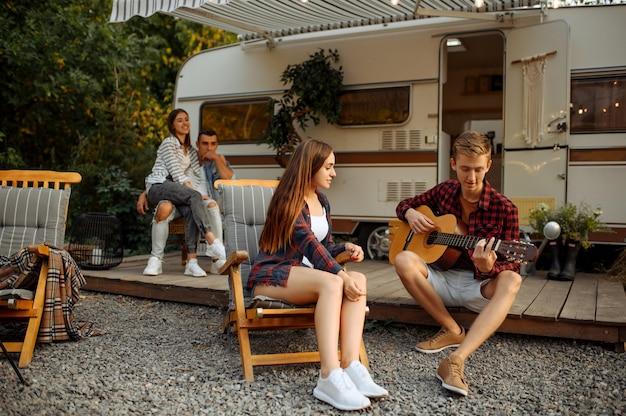 Amici che giocano alla chitarra sul picnic al campeggio nella foresta. gioventù avente avventura estiva in camper, camper due coppie di svaghi, viaggiando con rimorchio