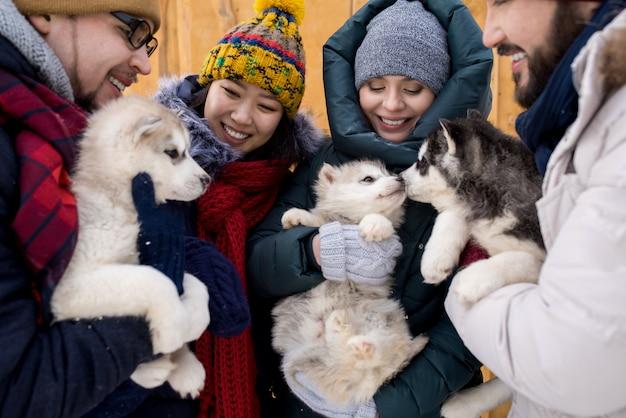Amici che giocano con simpatici cuccioli