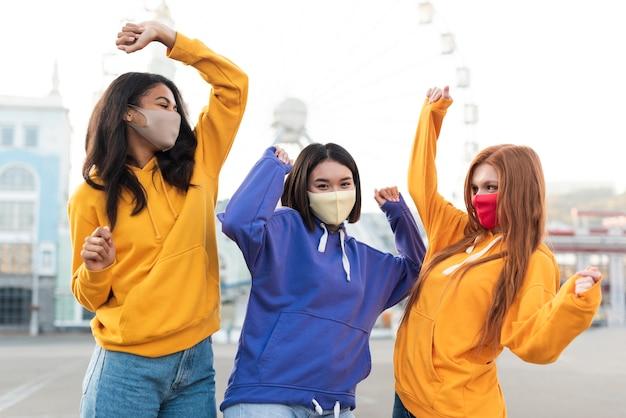 Amici in posa in modo divertente mentre indossano maschere mediche