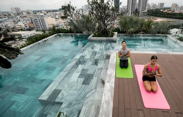 Amici che praticano yoga insieme all'aperto a bordo piscina